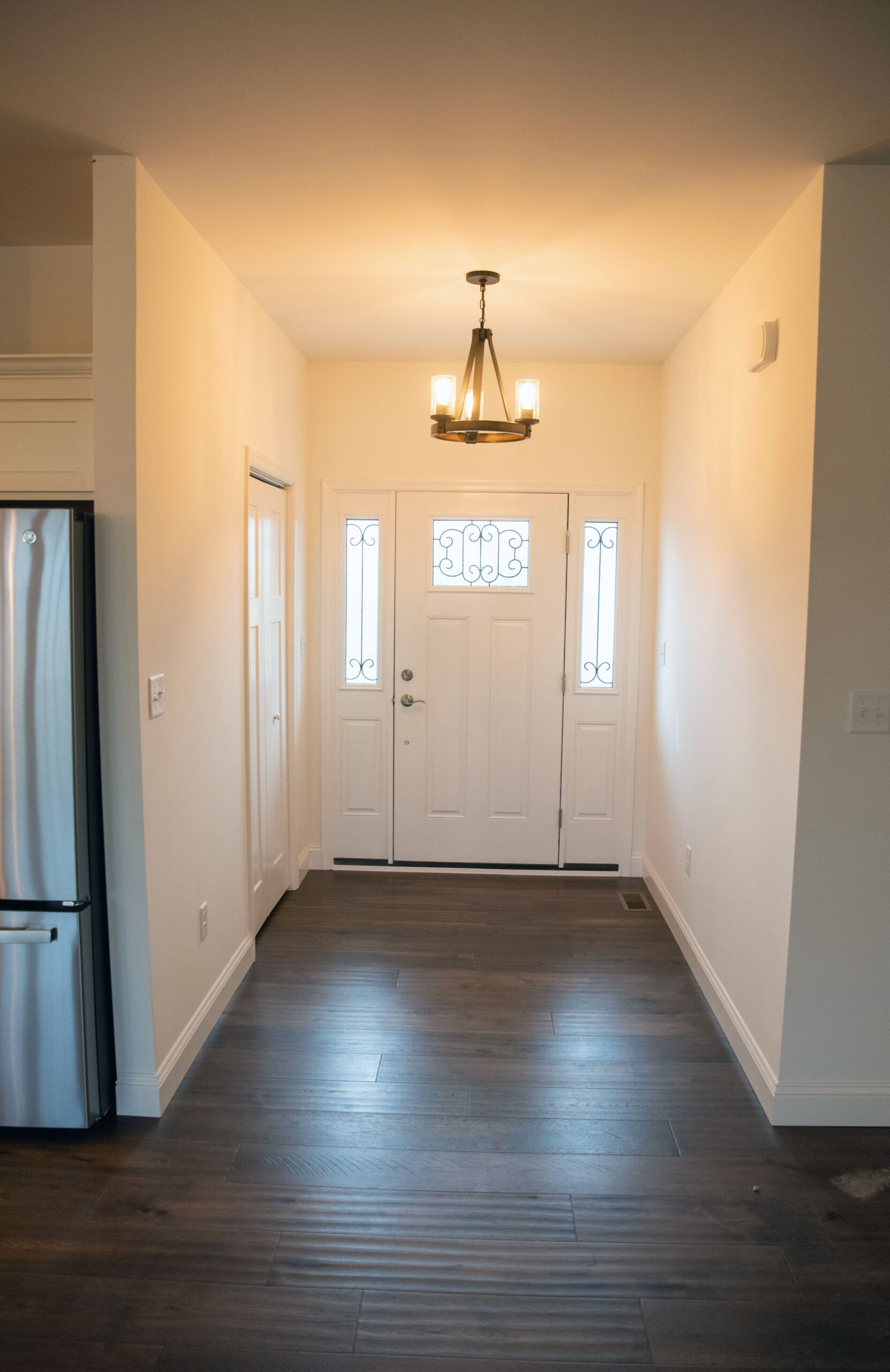 The foyer with an extra wide entry way with hardwood flooring, a chandelier and white walls