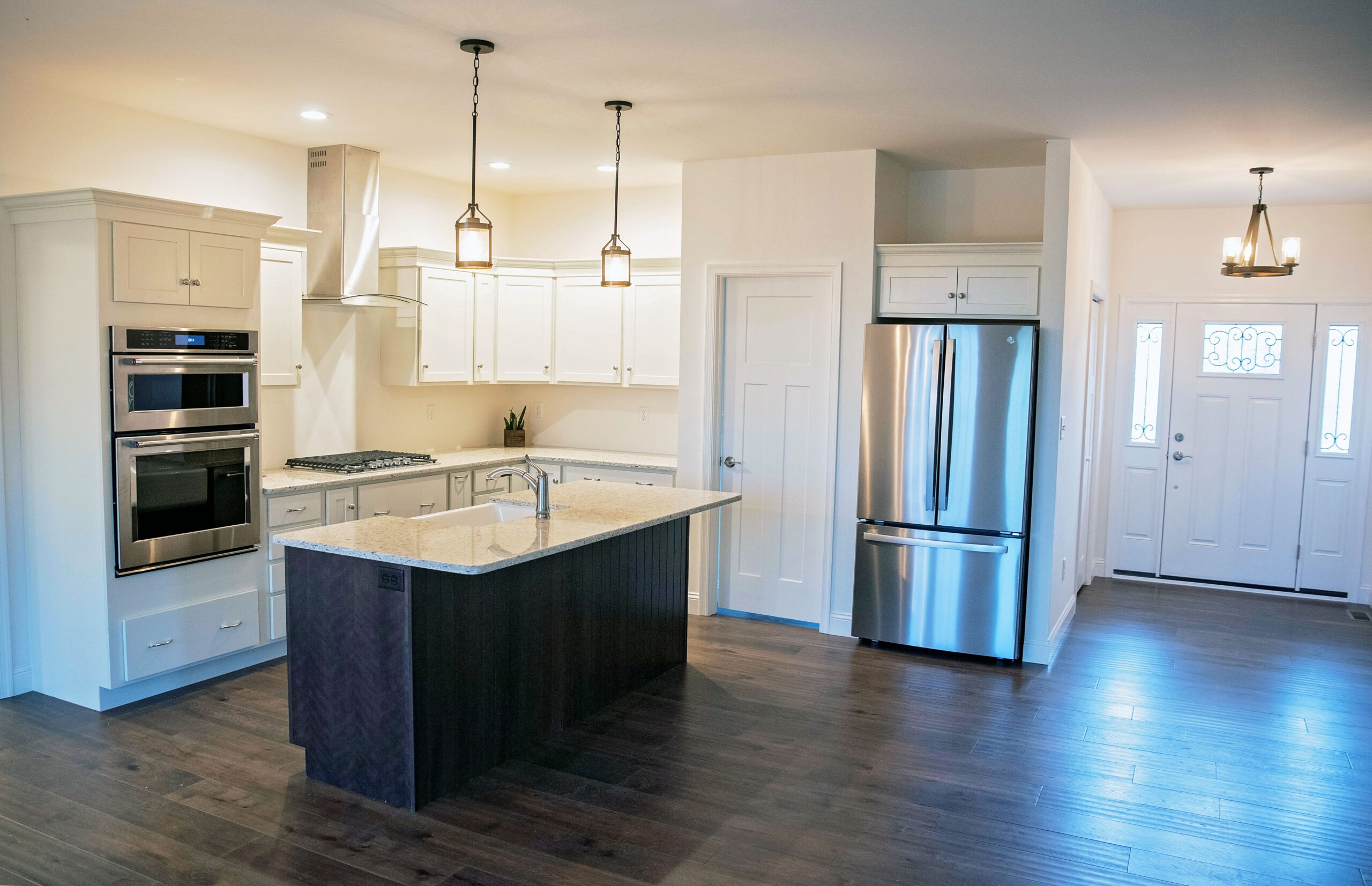 The 2-toned kitchen with white painted perimeter cabinets and a cherry stained island with quartz countertops.