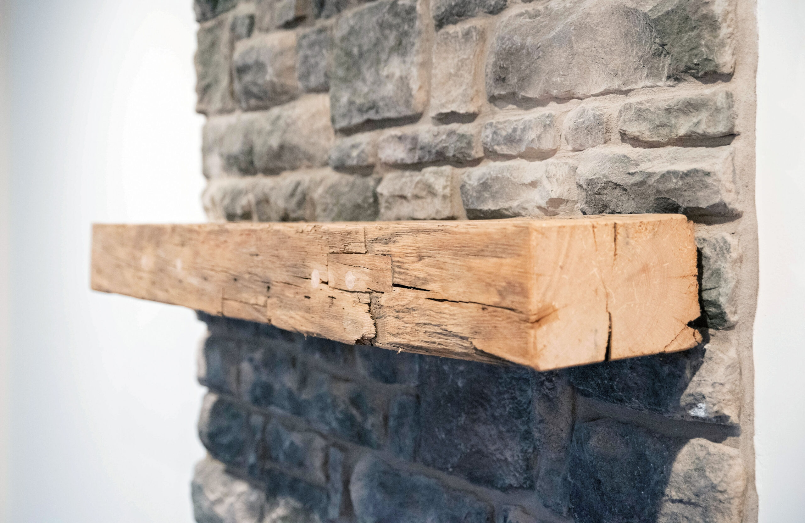 Up close picture of a repurposed, wood barn beam mantel supplied by Corrado Custom Homes.