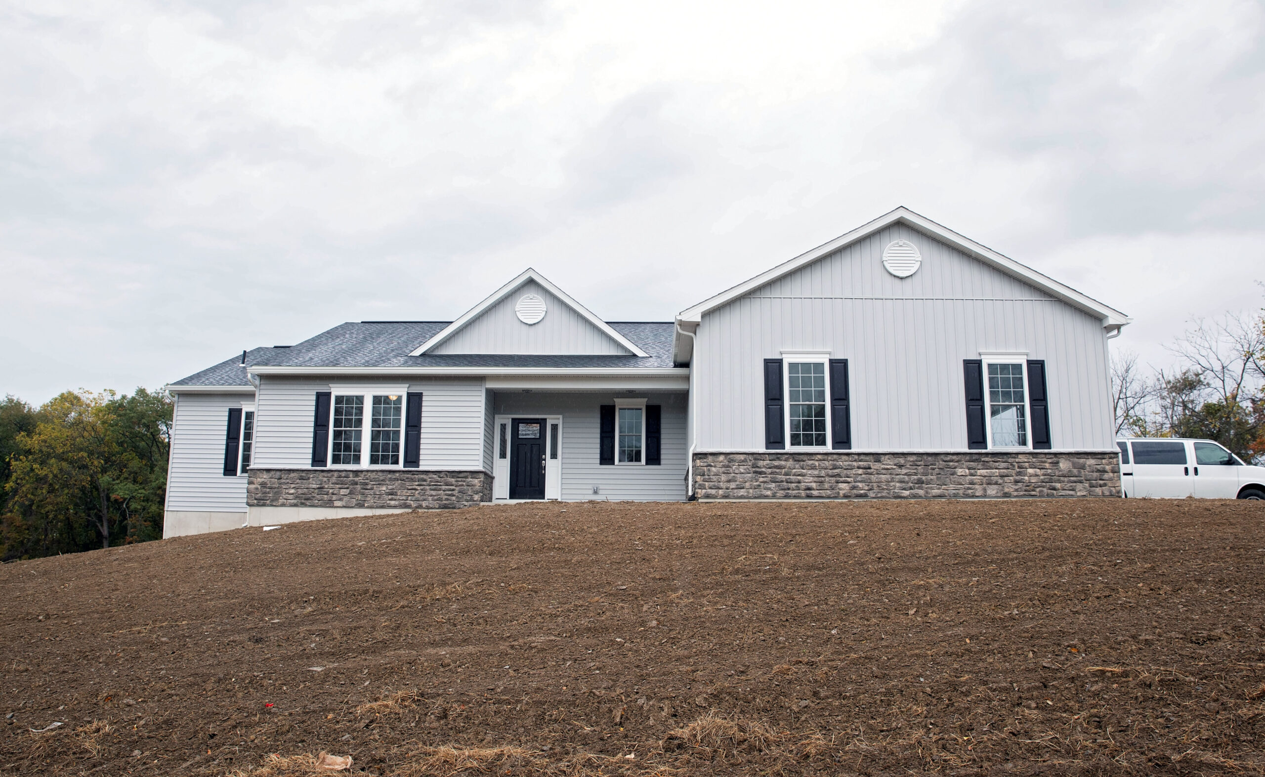 The front of a custom-built Lehigh Valley home with Board & Batten and clapboard vinyl siding and knee wall height stone.