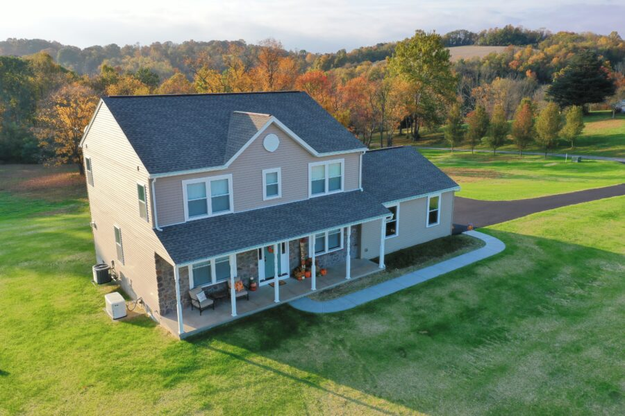 Bird's eye view of a a two story custom-built home with beige siding in Berks County with a covered front porch with stone and white trim.