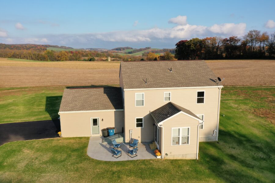 Bird's eye view of the back of a two story custom-built home in Berks County with beige siding and a bump-out and a large concrete patio.
