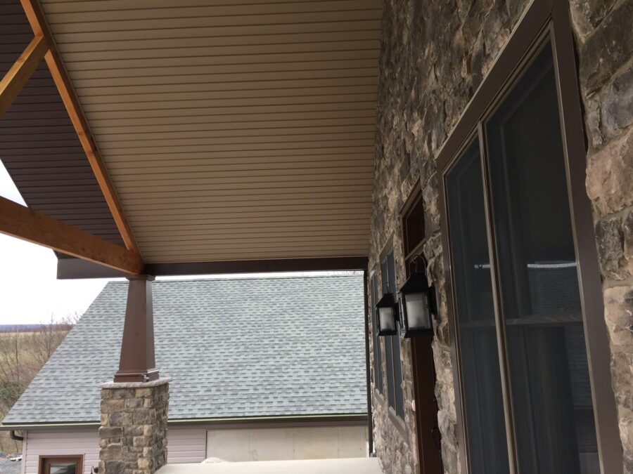 The underside of front porch roof infront of the stone wall and front door.