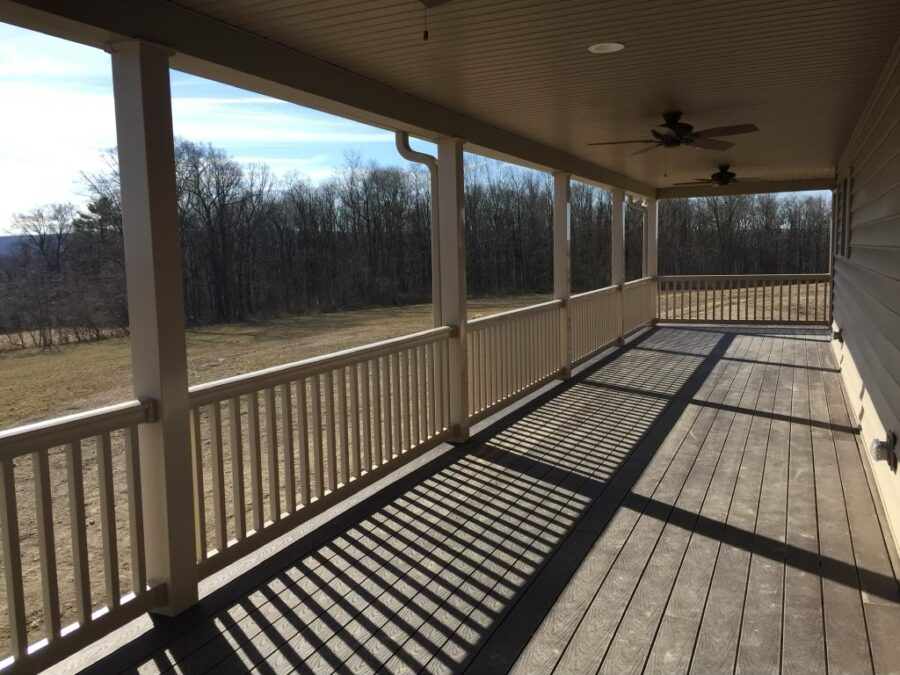 The rear covered patio with wood floors and ceiling fans overlooking the country scenery.