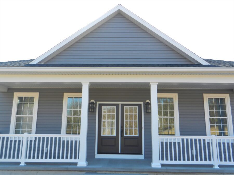 Front of a custom built Lehigh Valley home with a full front porch and white railing and white window trim.