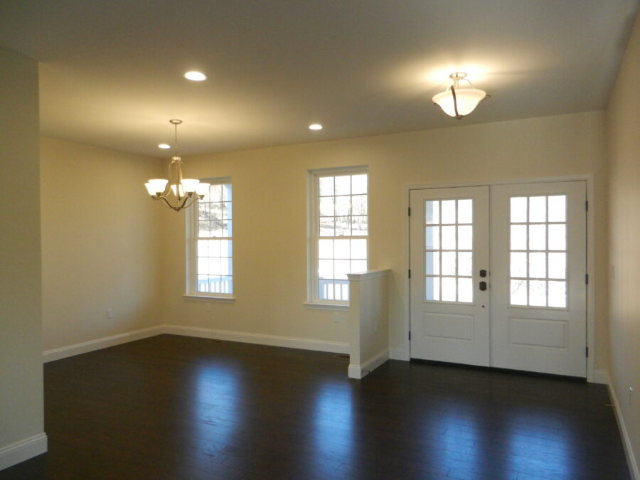 Open-concept view of the the foyer and dining room with white walls and hardwood floors.