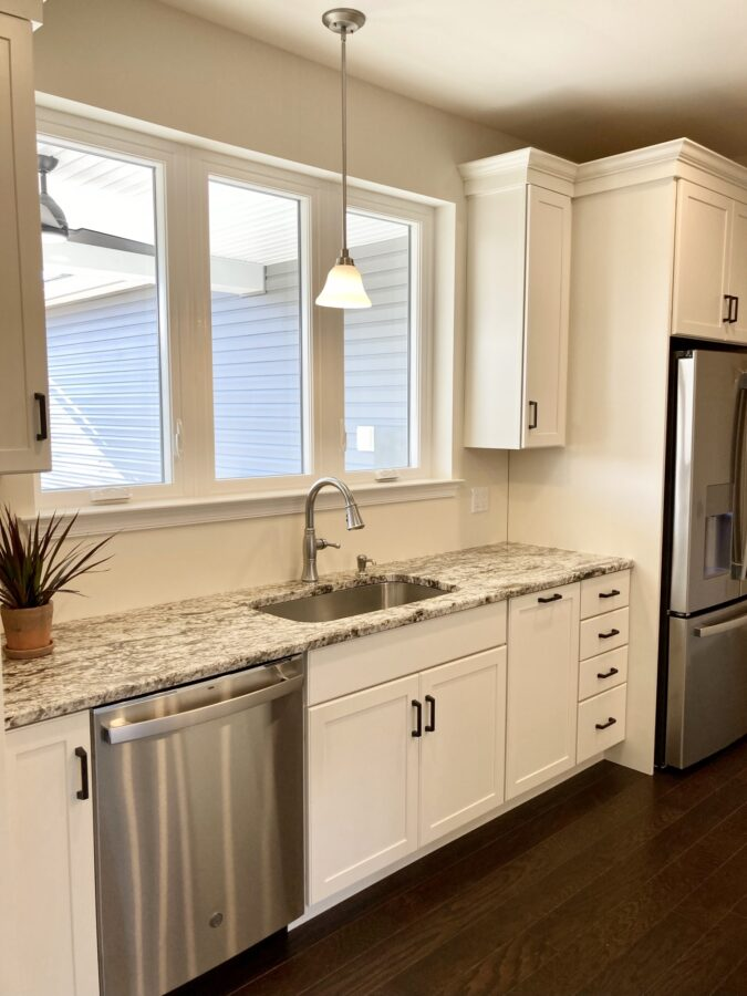 Sink wall in the custom built kitchen with super-sized single bowl kitchen sink. and white cabinetry.