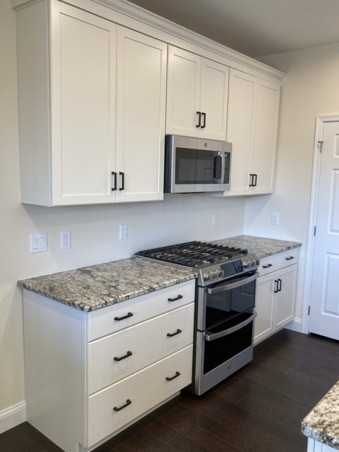 Range wall with oversized drawers, white cabinets, the stove and oven, and granite countertops.