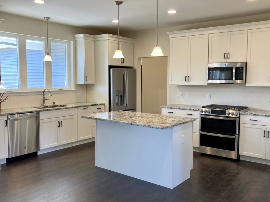 Custom designed kitchen with white painted maple cabinets and granite kitchen countertops and stainless steel appliances.