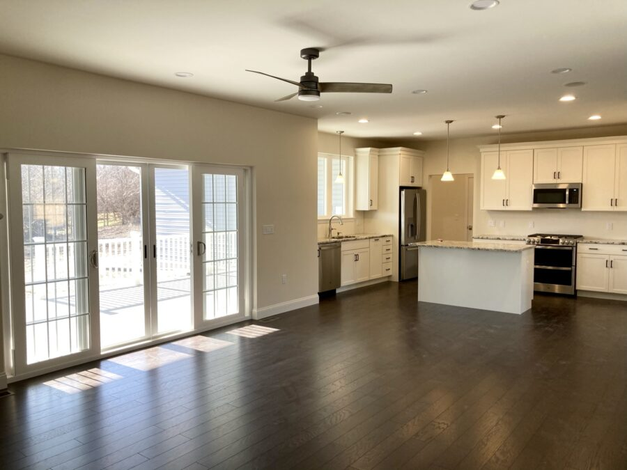 View from the great room into the kitchen area with engineered hardwood floors and the patio doors.