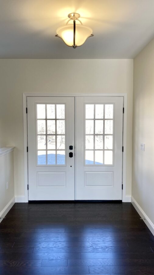 White double entry front doors with a ceiling light above it.