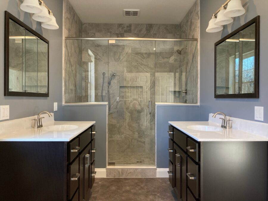 Master bathroom with a his-and-hers vanity and a tiled walk-in shower as the focal point.