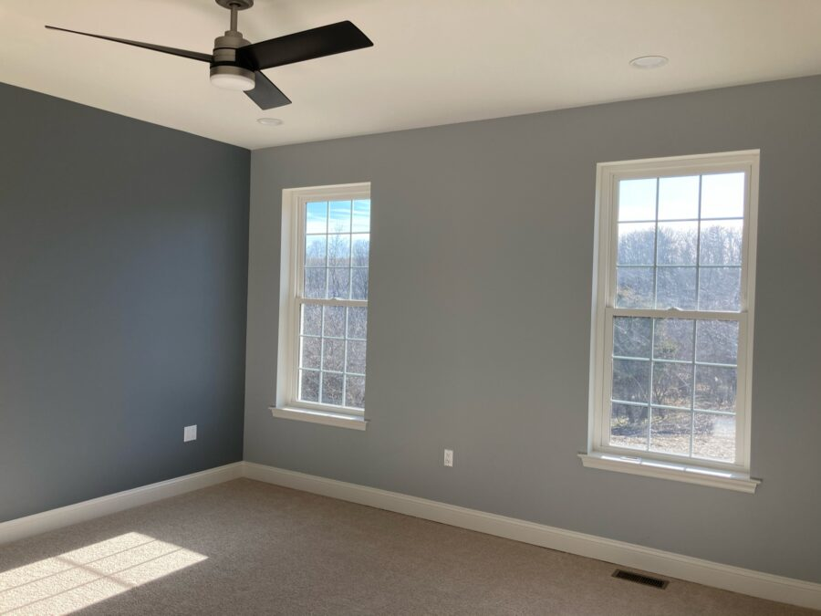 Master bedroom with upgraded carpet and paddingwith light grey walls, a slate accent wall and a ceiling fan.