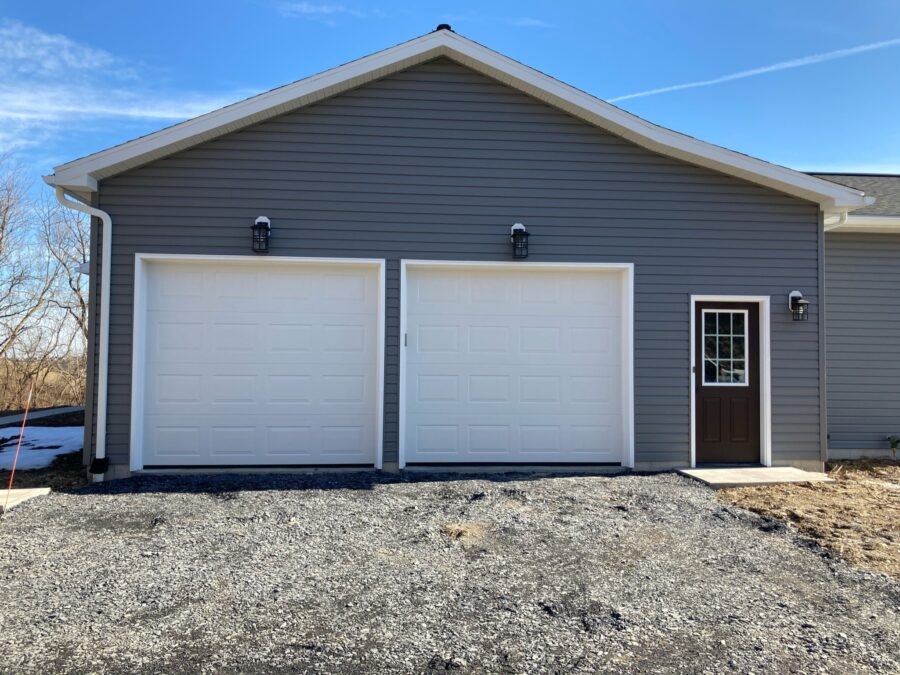 Garage Doors & Entry Door on a custom built home with grey siding and white trim