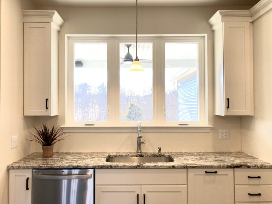 Sink wall in the custom built kitchen with Viwinco casement windows and white cabinets and a dishwasher.