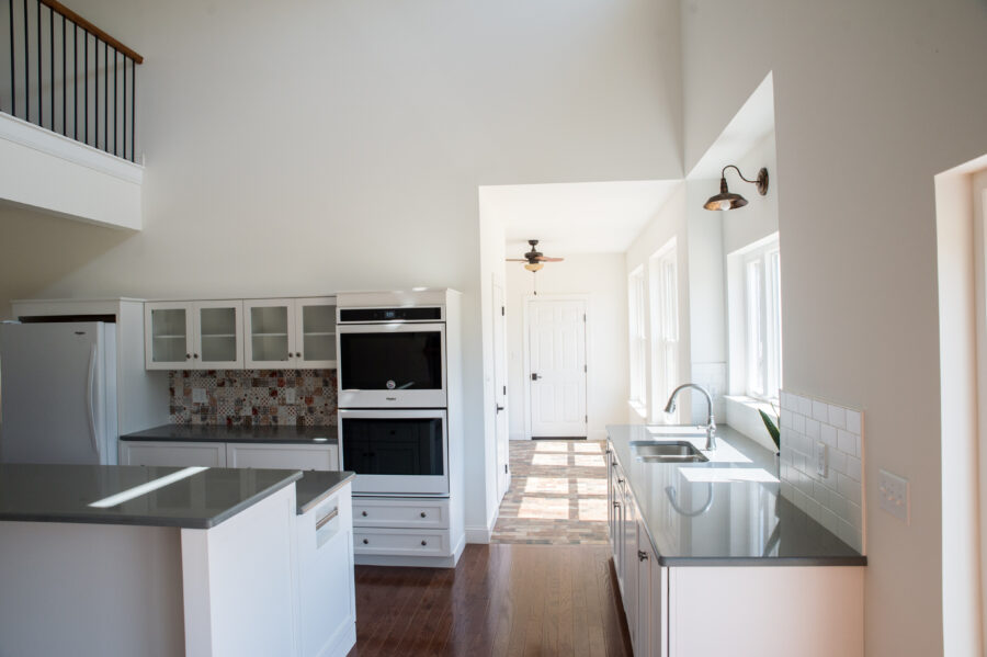 The custom-designed kitchen with white walls, white painted cabinets and quartz countertops viewing into the laundry room