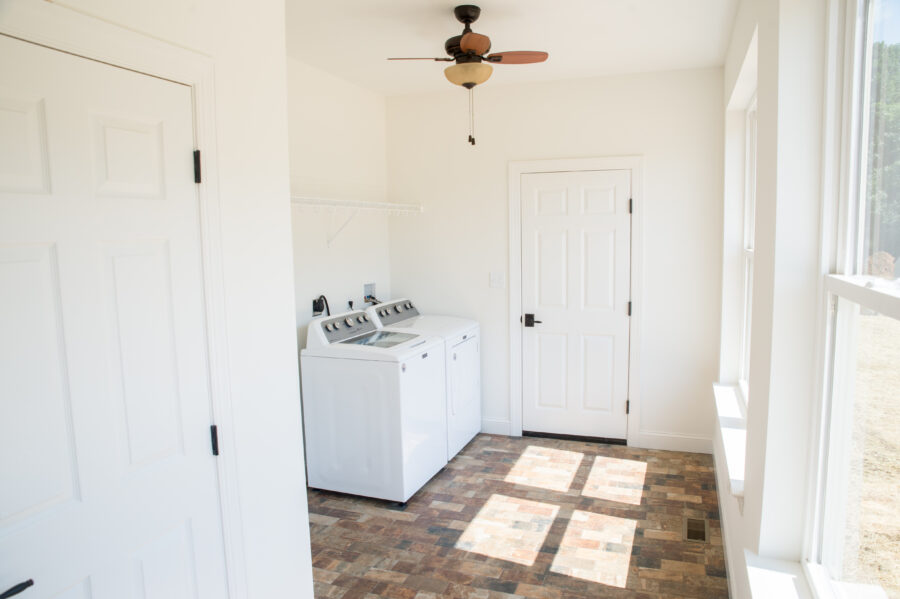 The laundry room with a full wall of windows and tile that looks like brick with a ceiling fan and a washer and dryer