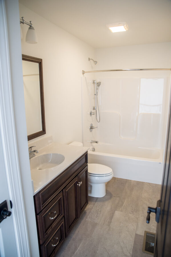 The kids' Bathroom with custom dark wood cabinetry, luxury vinyl tile flooring, and a white tub and shower and toilet