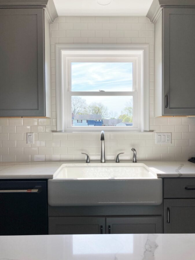 The Kohler, Apron-Front Farmhouse kitchen sink under a window with white trim and white subway tile and grey cabinets