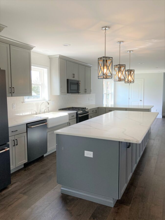 The kitchen with 8 foot high 1st floor walls with cabinetry to the ceiling and hardwood flooring with an oversized kitchen island.