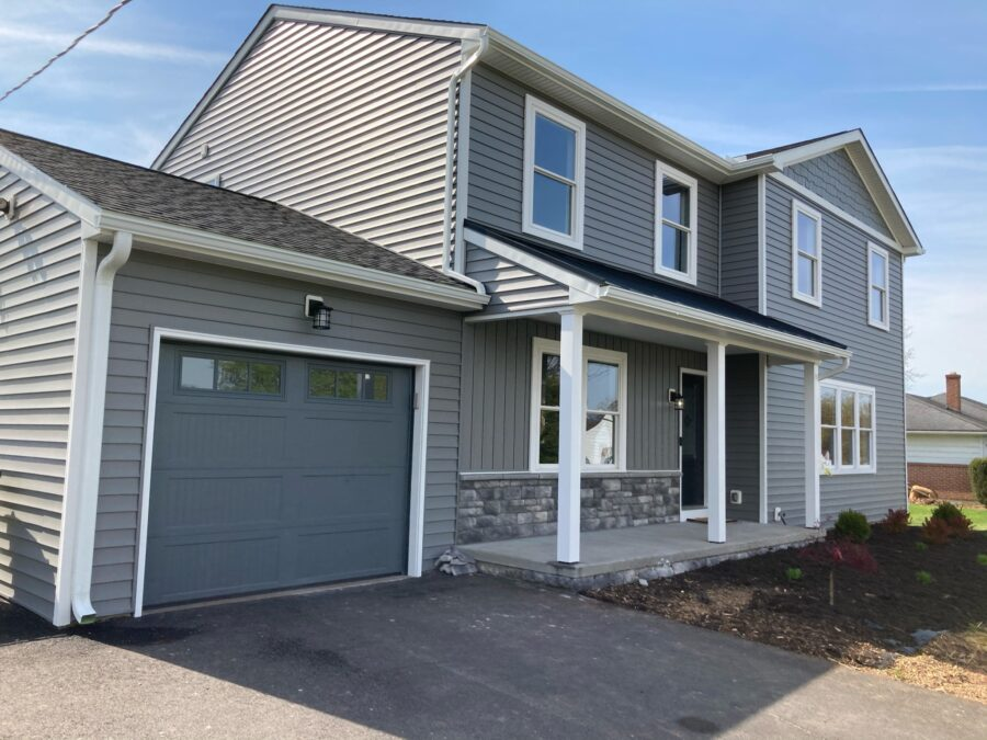 The front of a custom-built two-story home in Montgomery County featuring charcoal grey siding and white trim and a garage.