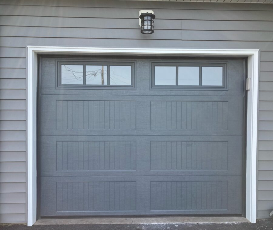 Charcoal garage door with windows by Haas Door Company and white trim