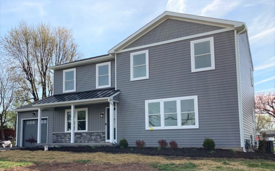 The front of a custom-built two-story home in Montgomery County featuring charcoal grey siding in horizontal, board & batten, and cedar shake styles.