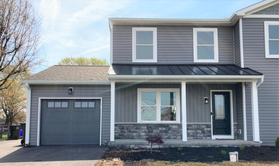 The front of a custom home with charcoal grey siding with metal roofing accents the front porch and grey custone style veneer stone under the front porch.