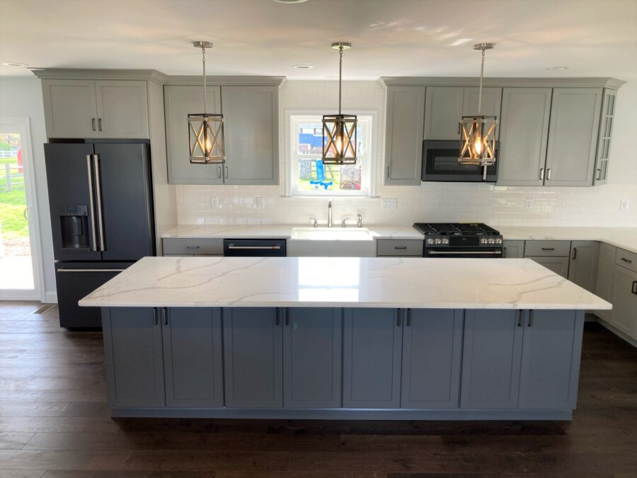 The kitchen with an oversized kitchen island with 2-Tone cabinetry with Moonstone colored island & Cloud colored Perimeter cabinetry by Kemper.