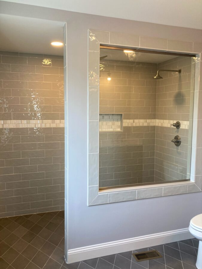 The Master Bathroom completed walk-in, curbless shower with tile that is on the floor and shower walls with a large glass panel