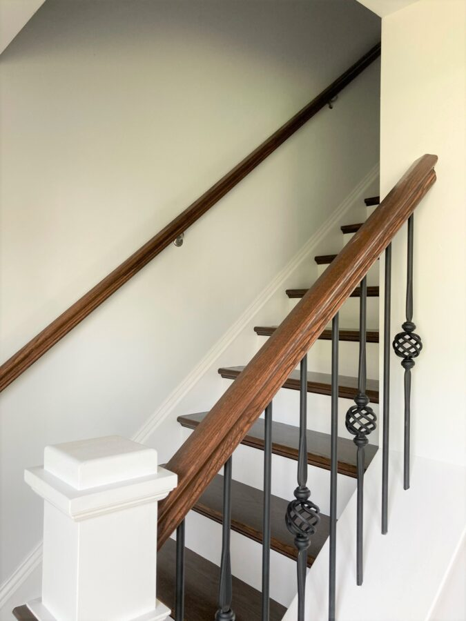 Oak treads and painted risers on the stairs with Craftsman box newel and iron balusters.