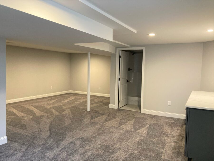 The completely finished basement with neutral carpets and walls and full finished bathroom.