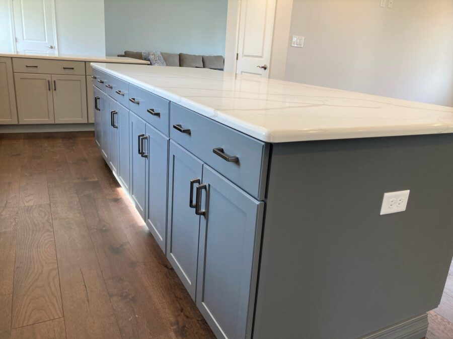 Amply storage drawers and cabinets in the oversized moonstone-colored kitchen island.