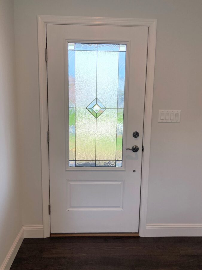 The upgraded Therma Tru-Smooth Star Door front door painted white on the interior to match the trim.